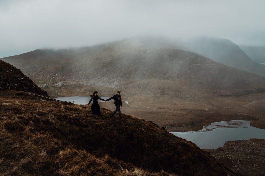 Isle of Skye Elopement - couple walking holding hands on top of mountain on The Isle of Skye.