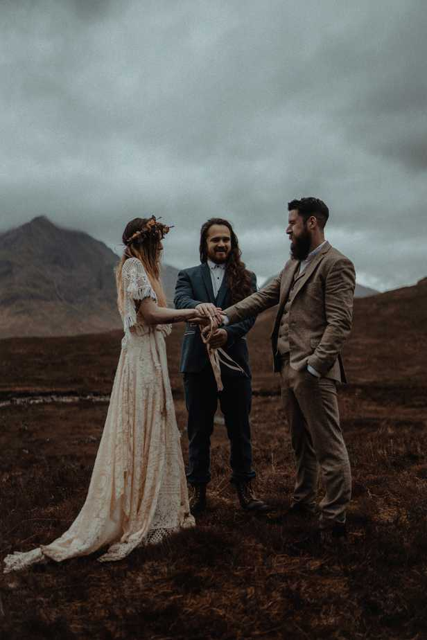 A couple and celebrant performing a Hand-fasting Ceremony during Isle of Skye Elopement
