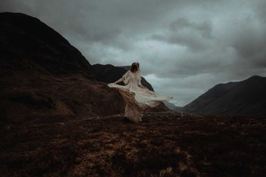 Glencoe Elopement Photographer. a bride twirling her dress around on top of a mountain in Glencoe.