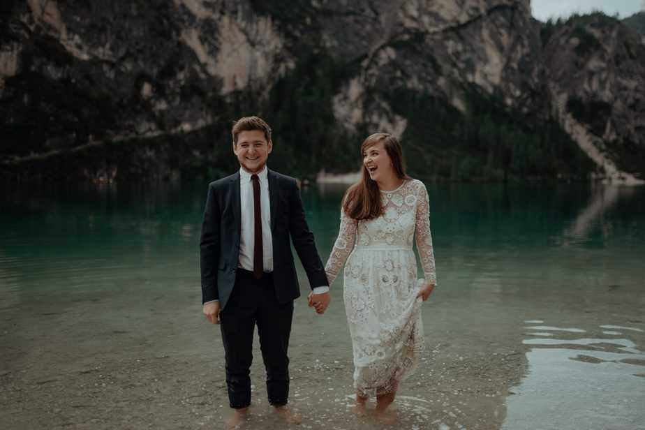 Destination Wedding Photographer. Couple standing in the water laughing at Lake Braies during their Elopement at Lake Braies, Italy.
