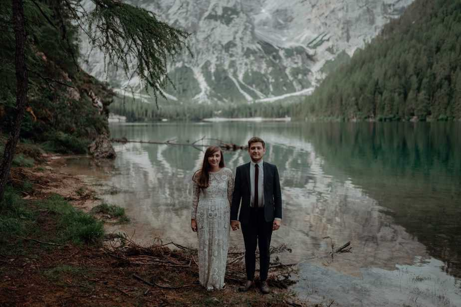 Couple standing next to lake during Destination Wedding at Lake Braies by Destination Wedding Photographer Belle Art Photography