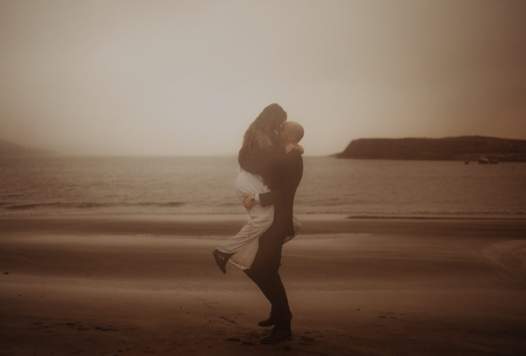 groom picking bride up on Staffin Bay during elopement on The Isle of Skye.