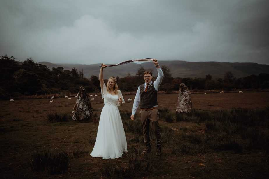 couple holding up handfasting ribbon at their Isle of Mull Elopement