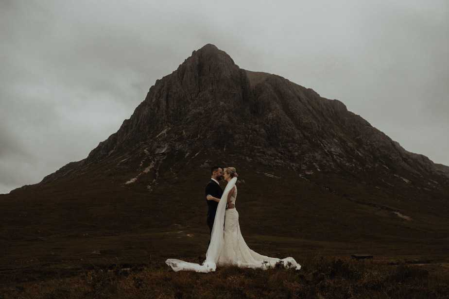 Couple stood underneath mountain in Glencoe during elopement by Isle of Skye Wedding Photographer