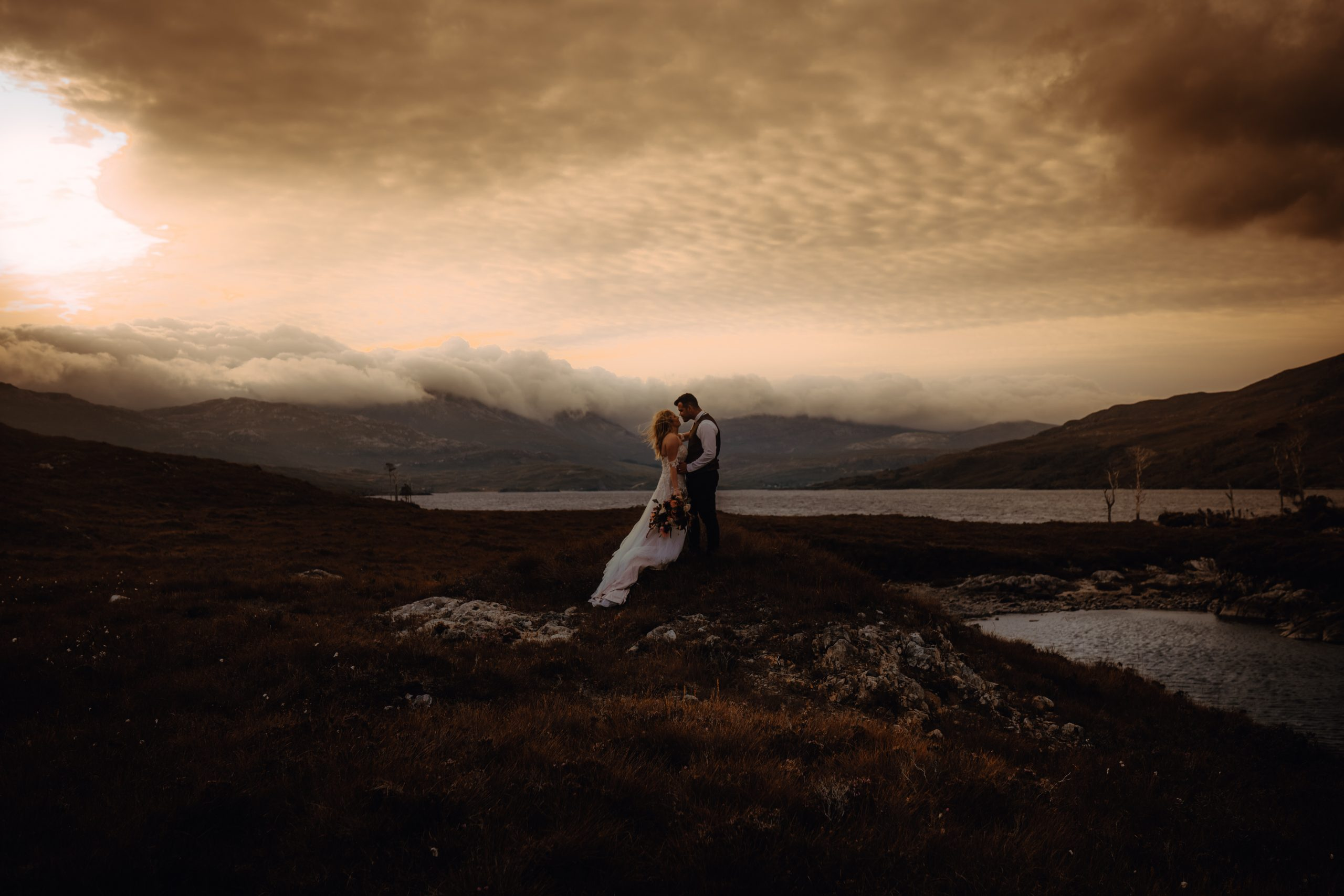 Loch Assynt Elopement, couple standing in front of loch at Sunrise