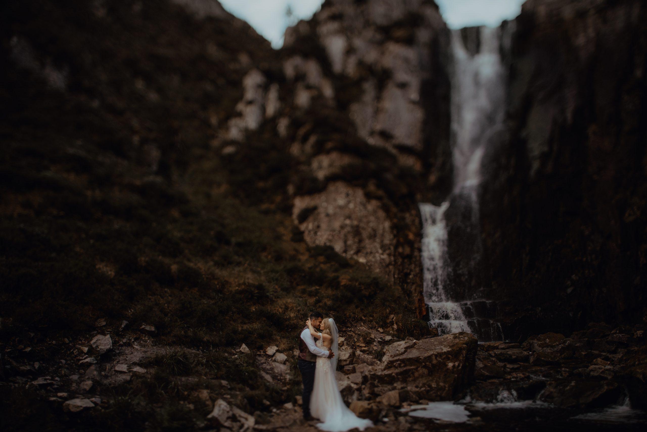 couple hugging under wailing widows Falls by Scotland Elopement photographer