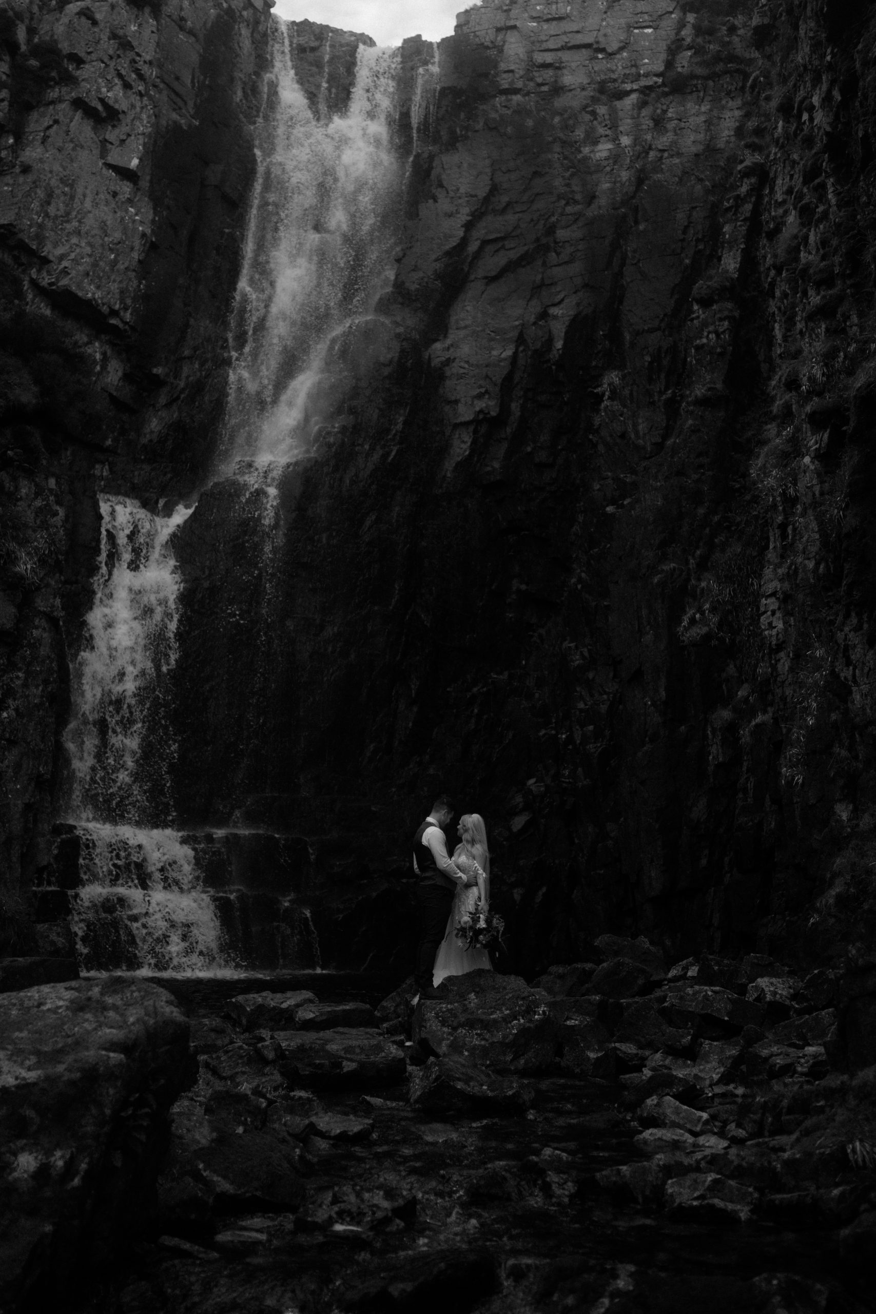 couple stood under Wailing Widow Falls, Assynt