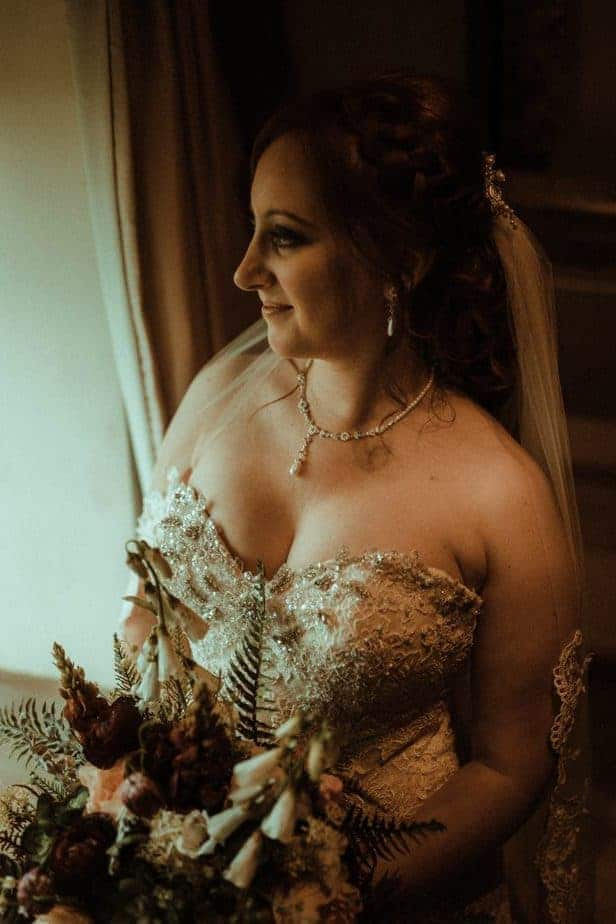 An image of the bride standing at the window at Crook Hall by Belle Art Photography
