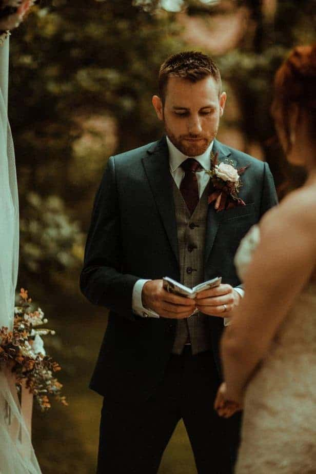 An image of the groom reading his vows at Crook Hall by Belle Art Photography
