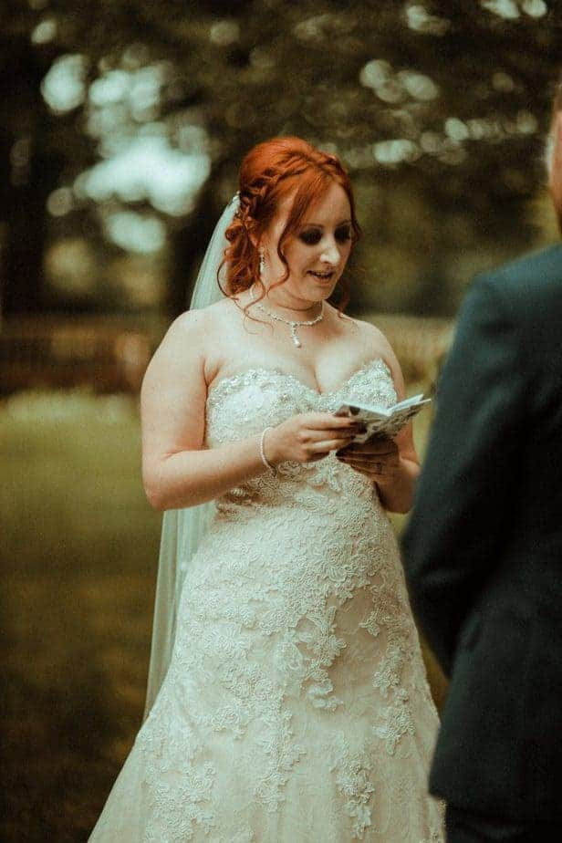 An image of the bride reading her vows at Crook Hall by Belle Art Photography