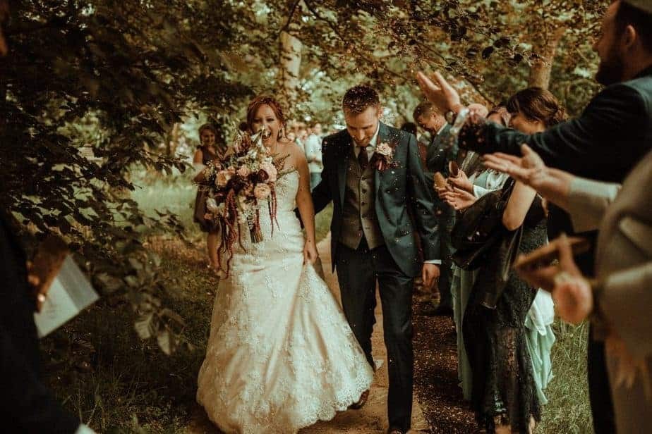An image of people throwing confetti at bride and groom at Crook Hall by Belle Art Photography