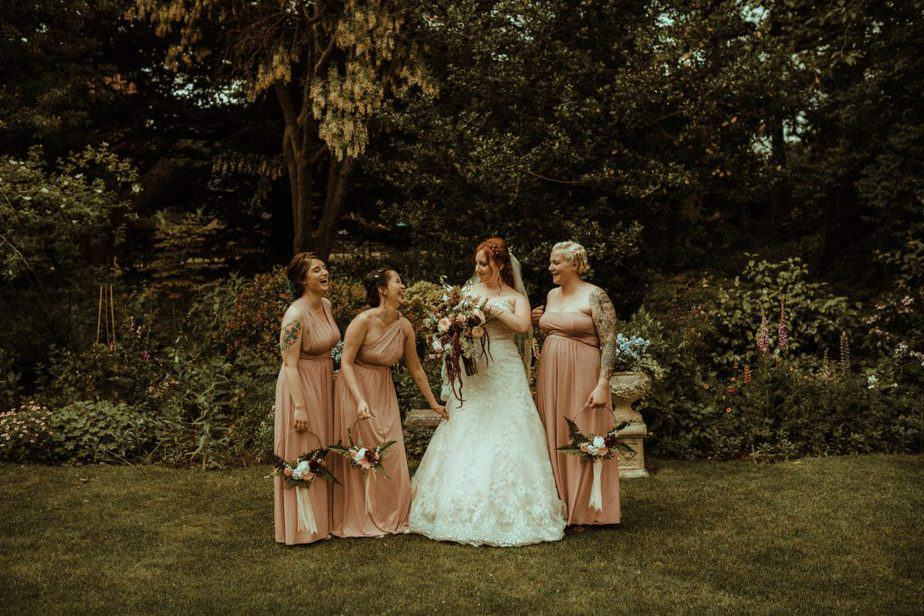An image of the bride and bridesmaids laughing at Crook Hall by Belle Art Photography