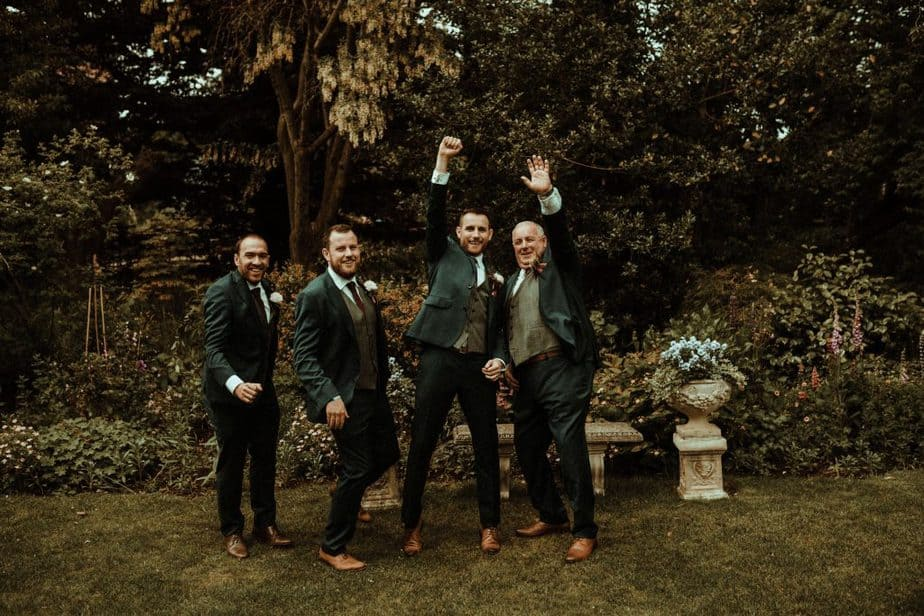 An image of the groom and best man jumping at Crook Hall by Belle Art Photography