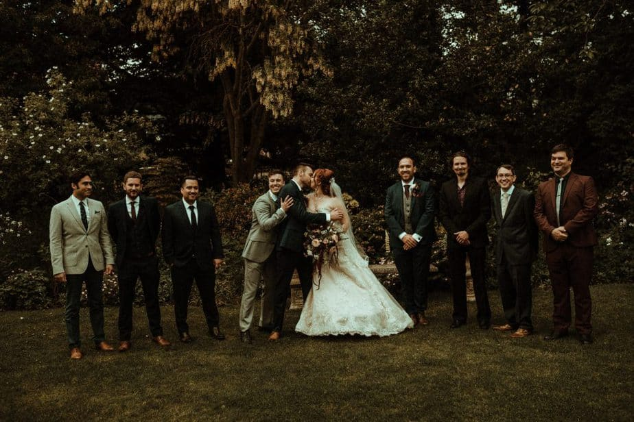 An image of bride and groom kissing with friends at Crook Hall by Belle Art Photography