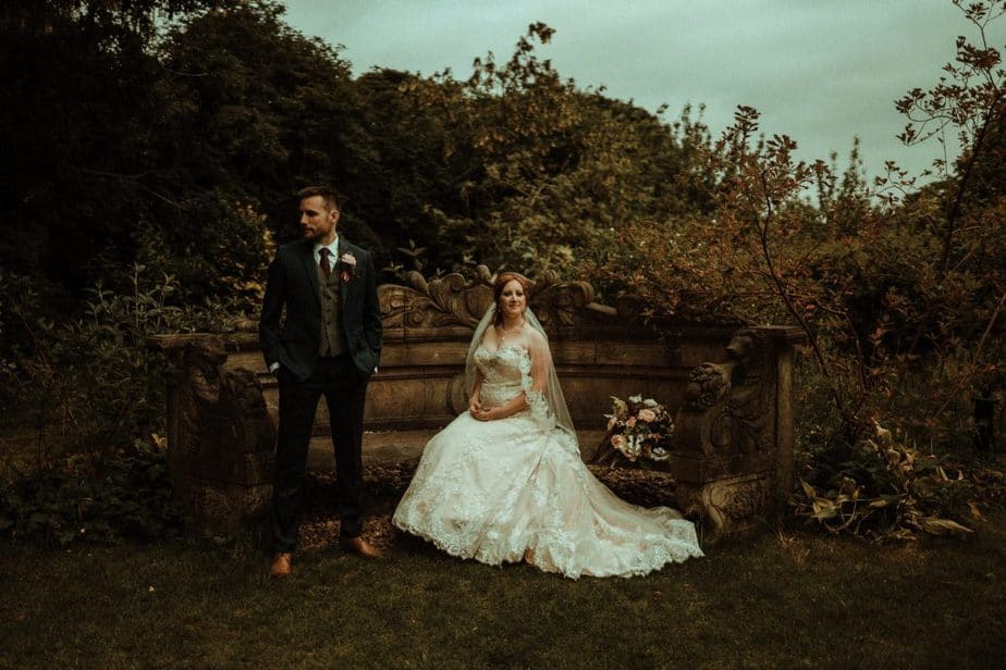 An image of bride and groom sitting on a bench at Crook Hall by Belle Art Photography