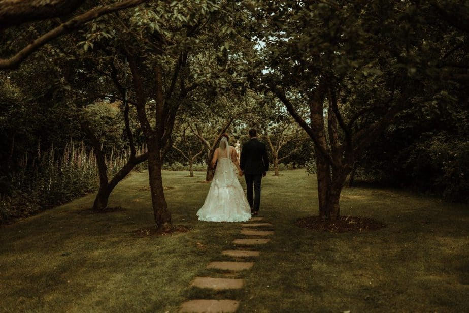 An image of bride and groom walking at Crook Hall by Belle Art Photography