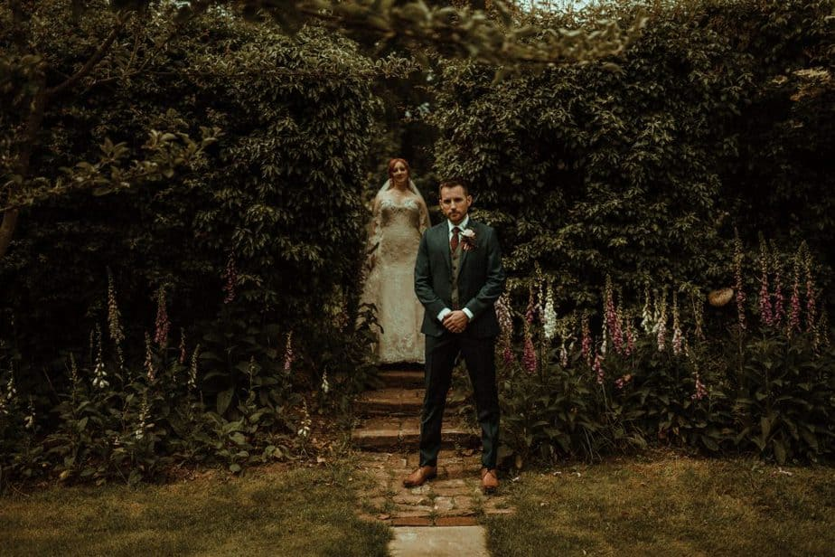 An image of bride standing behind groom at Crook Hall by Belle Art Photography