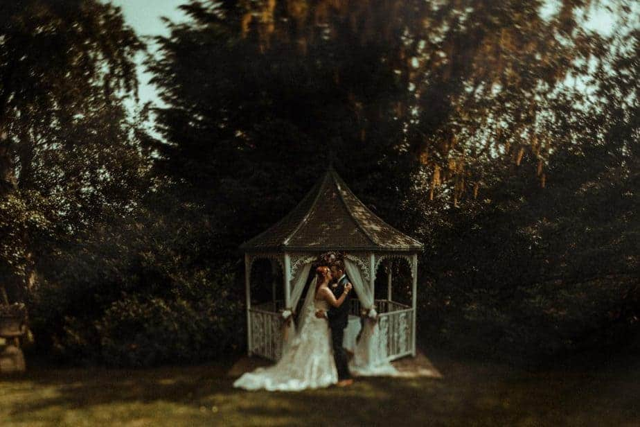 An image of bride and groom kissing by alter at Crook Hall by Belle Art Photography