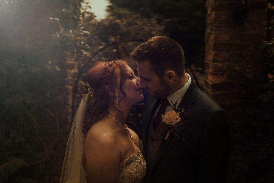 An image of bride and groom kissing at the gate at Crook Hall by Belle Art Photography