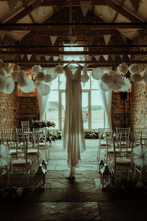 An image of the wedding dress hanging in the barn an intimate wedding at Northside Farm by Belle Art Photography