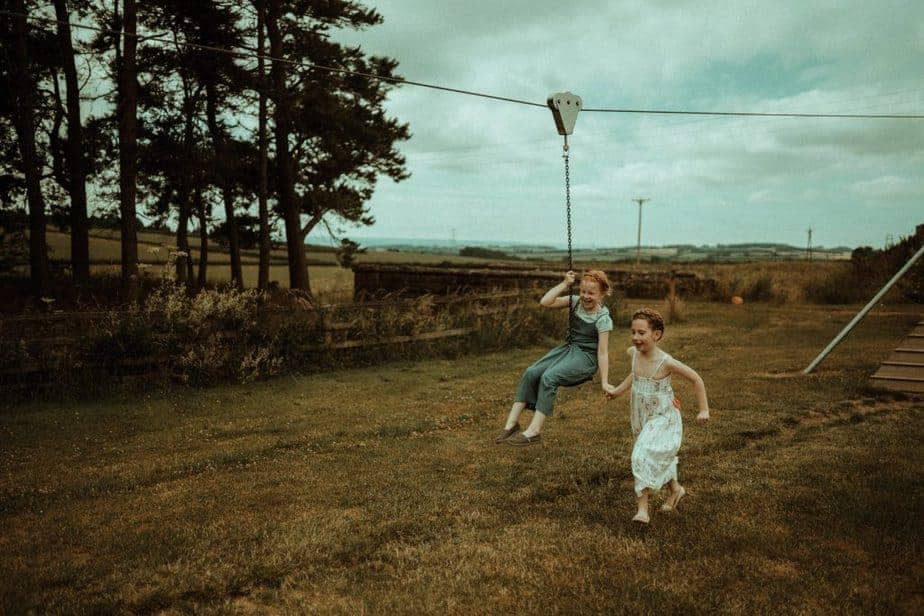 An image of kids playing on swing an intimate wedding at Northside Farm by Belle Art Photography