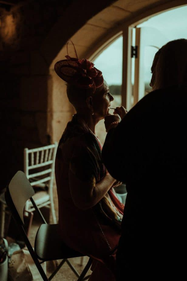 An image of mother of bride getting makeup on an intimate wedding at Northside Farm by Belle Art Photography
