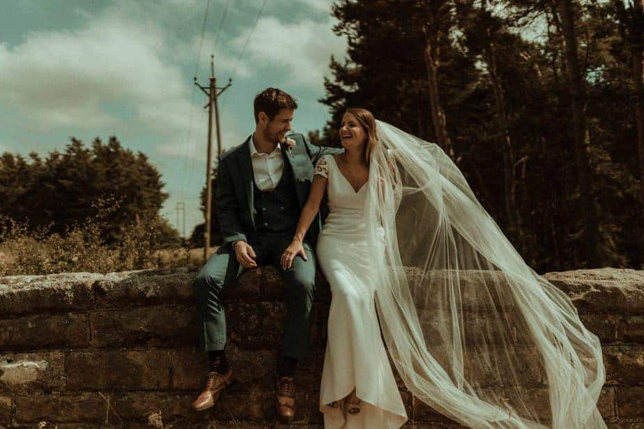An image of bride and groom sat on wall an intimate wedding at Northside Farm by Belle Art Photography