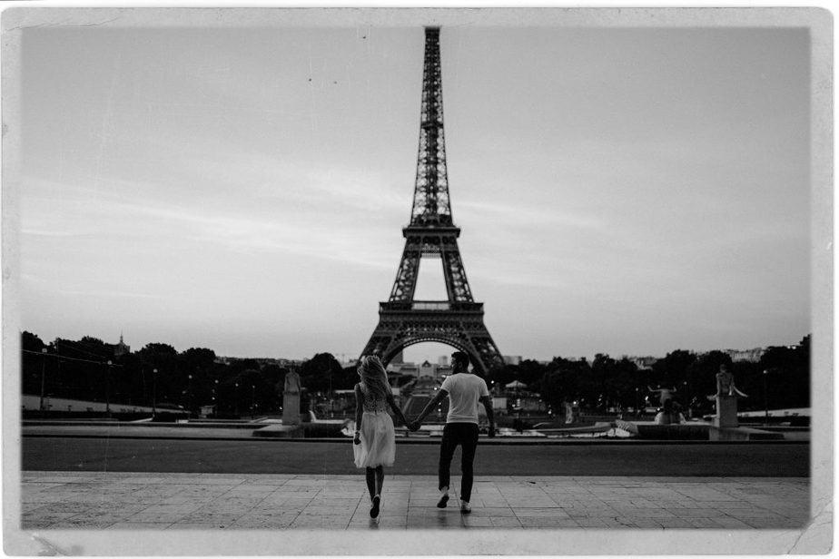 Man and women running towards Eiffel Tower, Paris. By Belle Art Photography