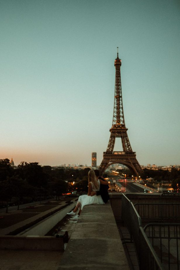 A couple sat on a wall looking at The Eiffel Tower at Sunrise, By Belle Art Photography