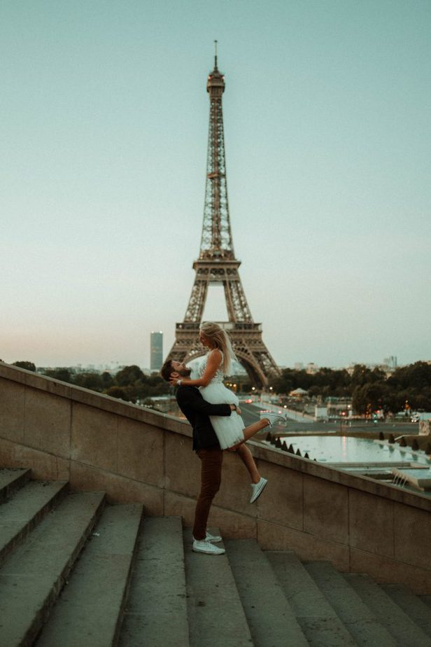 A couple standing on the steps looking at The Eiffel Tower at Sunrise, By Belle Art Photography