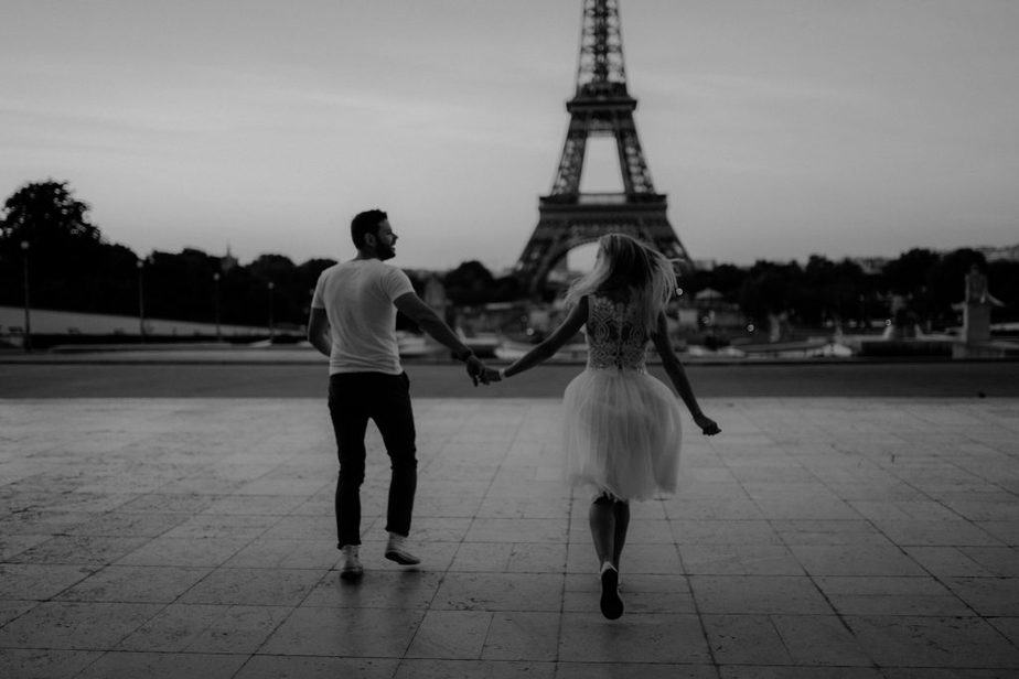 Couple running towards Eiffel Tower Paris Engagement Shoot by Belle Art Photography