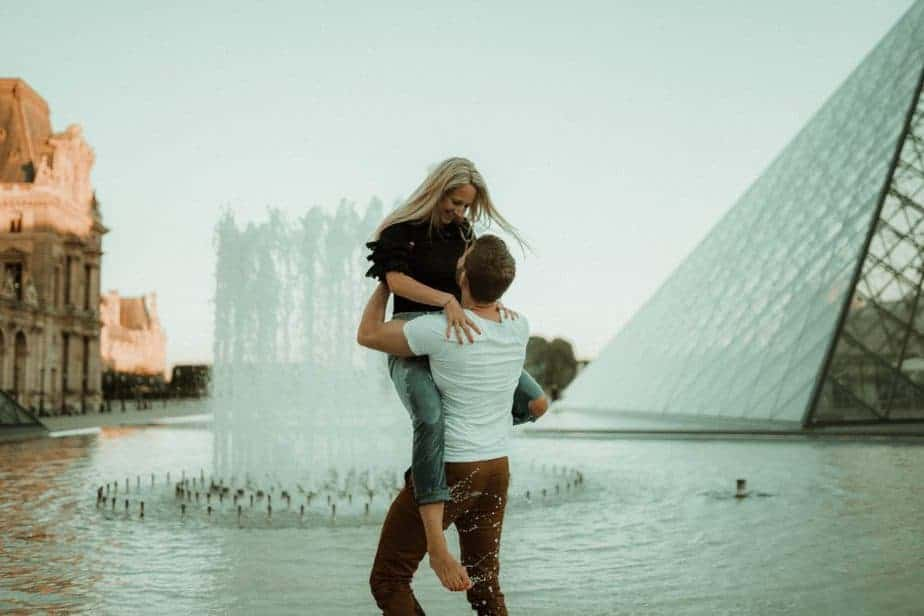 A couple splashing water at The Louvre for Paris Engagement Shoot by Belle Art Photography