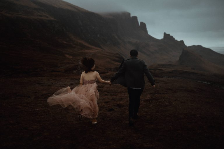 Couple running across mountain during Isle of Skye Elopement by Belle Art Photography