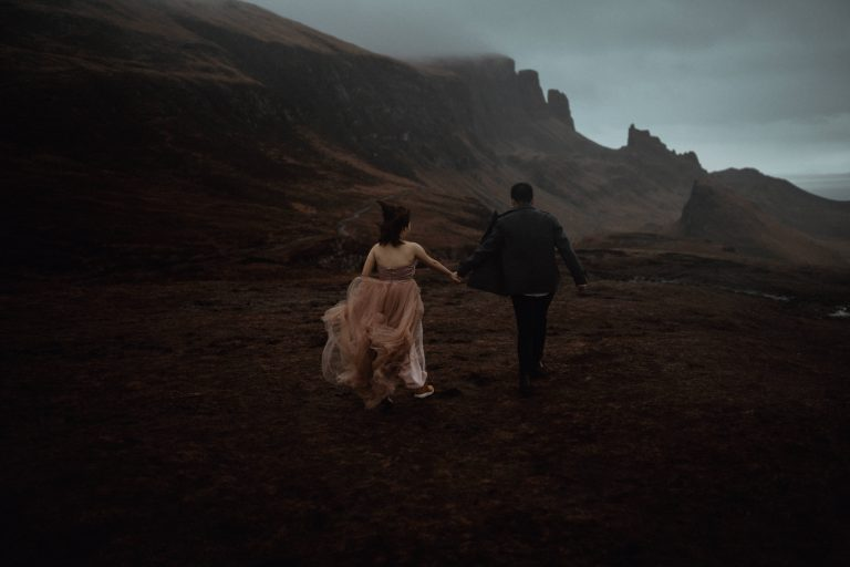 Couple running together across The Quiraing during Isle of Skye Elopement