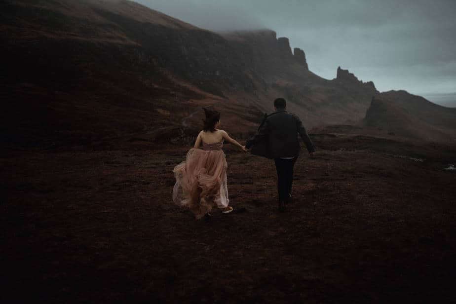 couple eloping at The Quiraing, running together holding hands across the top of The Quiraing.