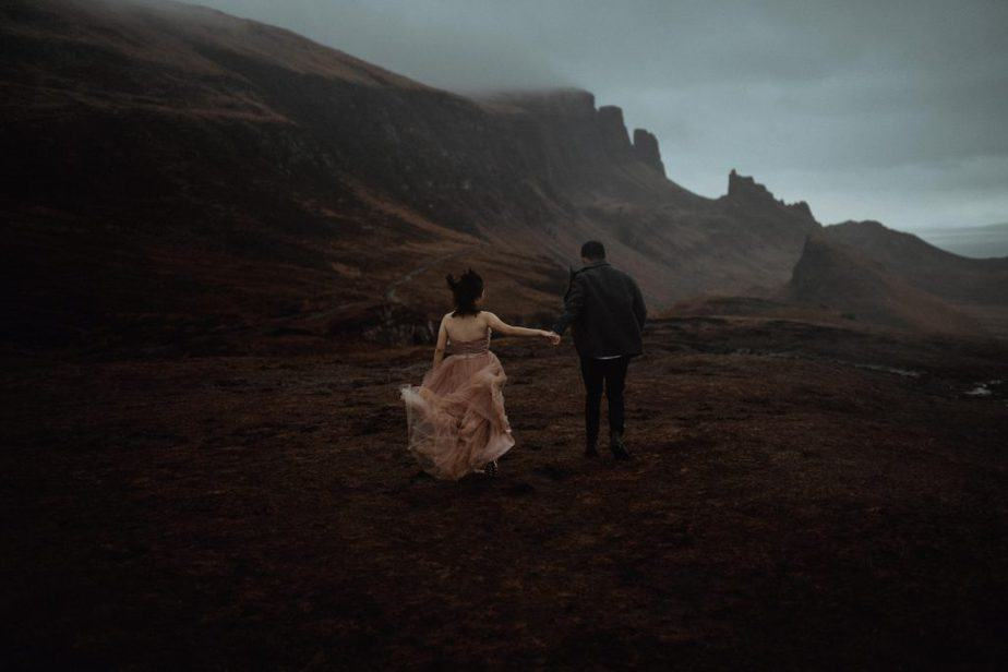 Couple running across mountain during moody Quiraing Elopement.
