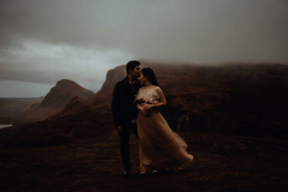 Couples hugging to keep warm during stormy elopement on The Isle of Skye.
