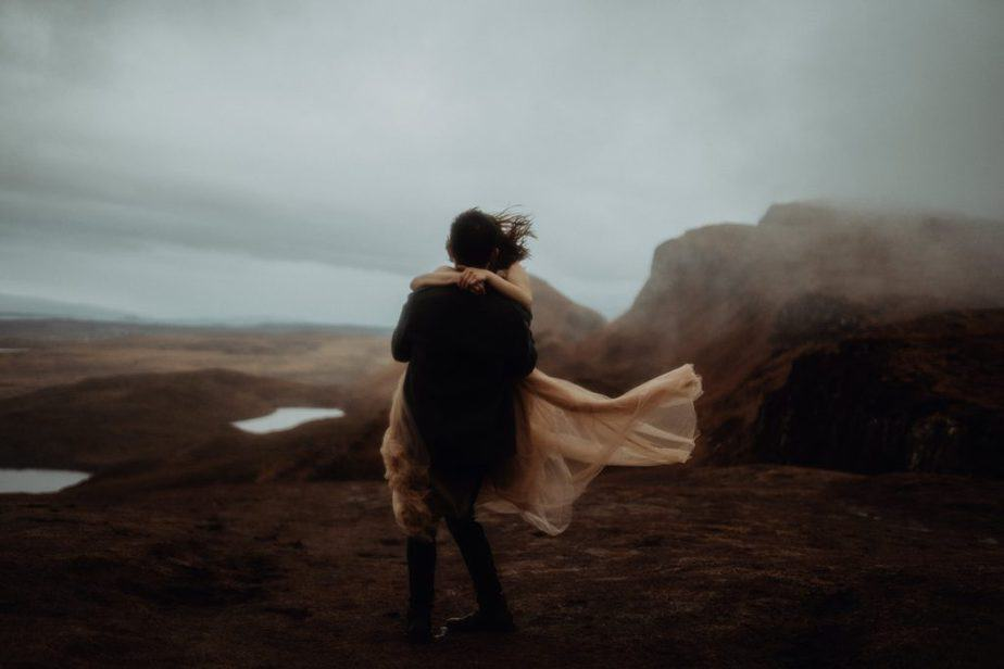 Man picking up Woman during storm at their Elopement on The Isle of Skye by Belle Art Photography