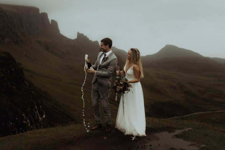 Couple popping champagne on The Quiraing celebrating their Isle of Skye Elopement