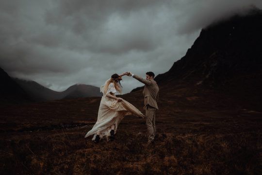 A Couple twirling in Glencoe by Scottish Highland Elopement Photographer