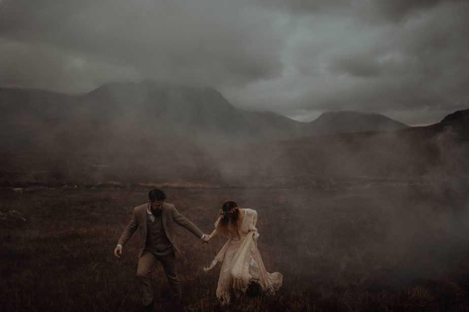A couple running through fog in Glencoe, Scotland by Scotland Wedding Photographer