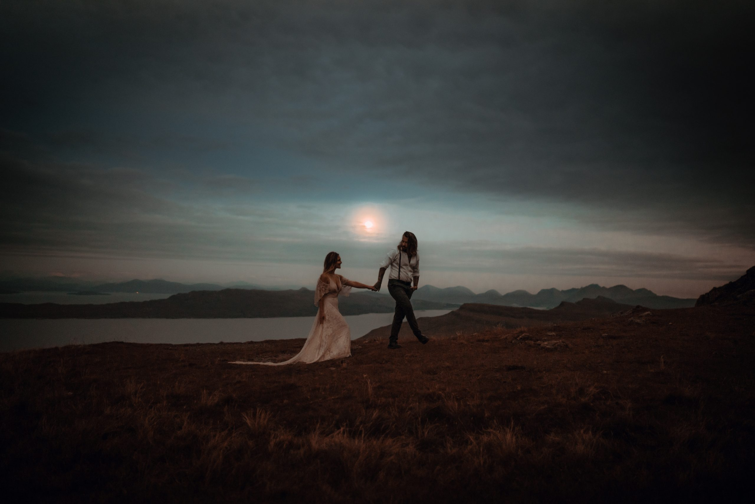 How to elope on The Isle of Skye - couple holding hands and walking past the moon on Storr