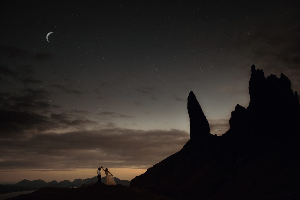 Sunset Elopement Old Man of Storr. Couple dancing on top of Storr during sunset with moon and stars in background.