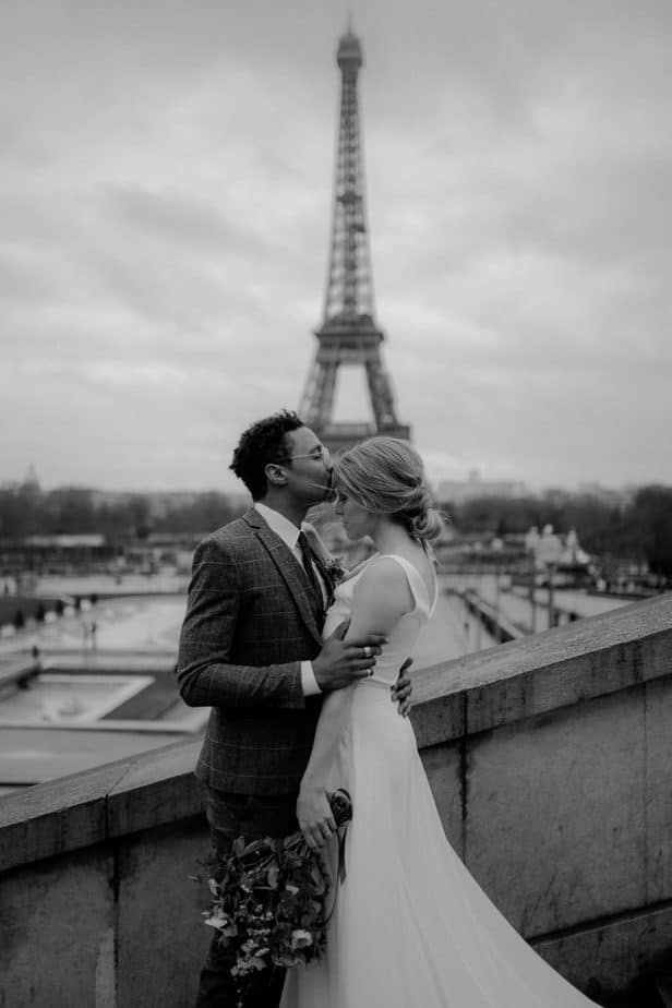 Couple kissing in front of Eiffel Tower by Paris Elopement Photographer - Belle Art Photography
