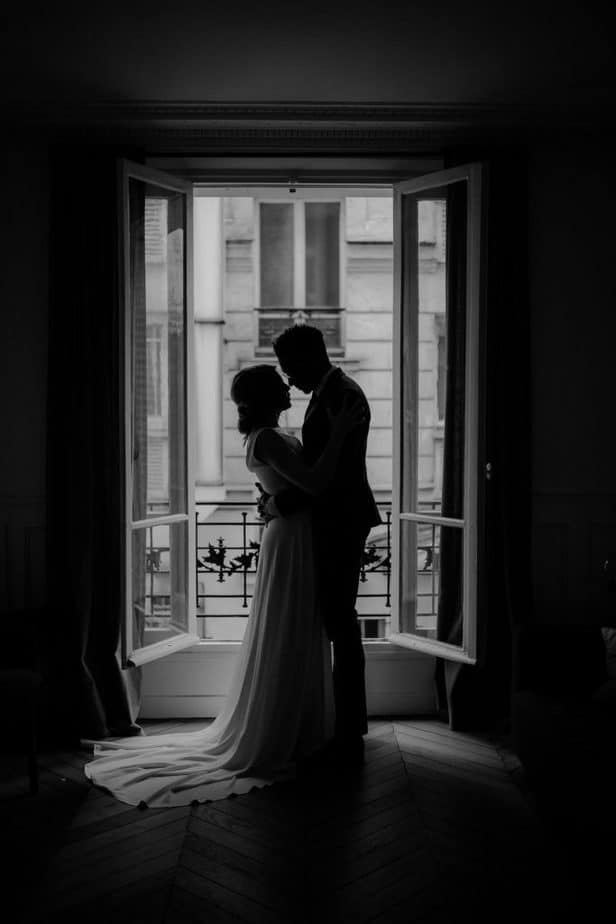 Silhouette of couple standing in the French window of their Paris apartment before they get married.
