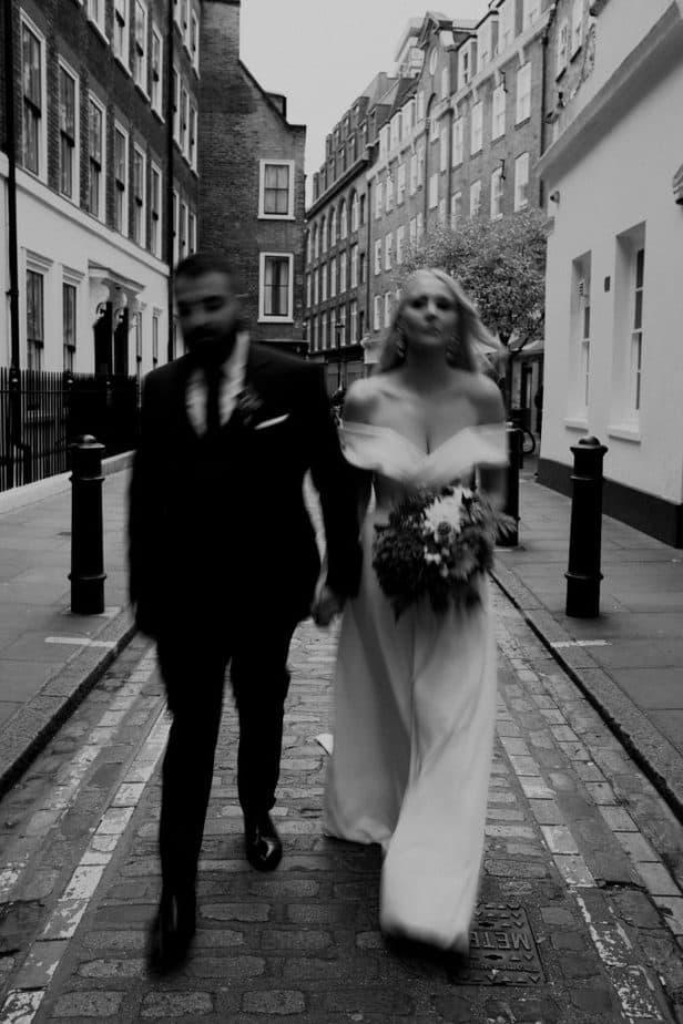 Couple walking through Shoreditch for wedding photographs