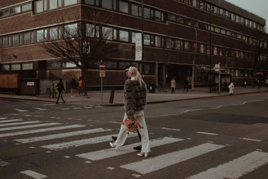 Couple walking across London crossing to elope in Shoreditch.