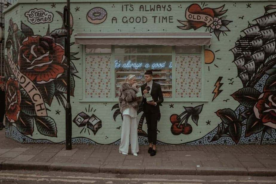 Couple eating donuts during Shoreditch elopement by London Elopement Photographer - Belle Art Photography