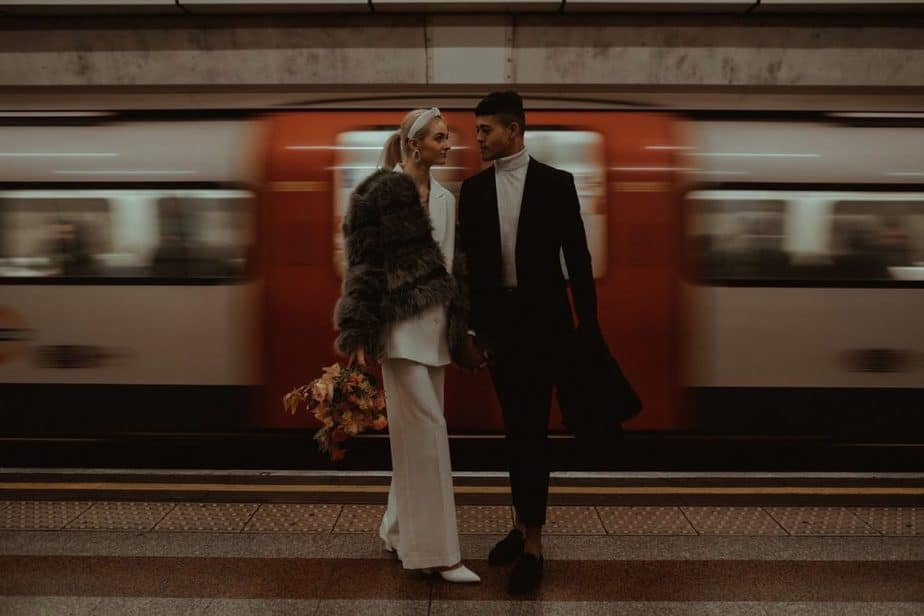 Couple stood in front of moving tube during London Elopement - by London Elopement Photographer
