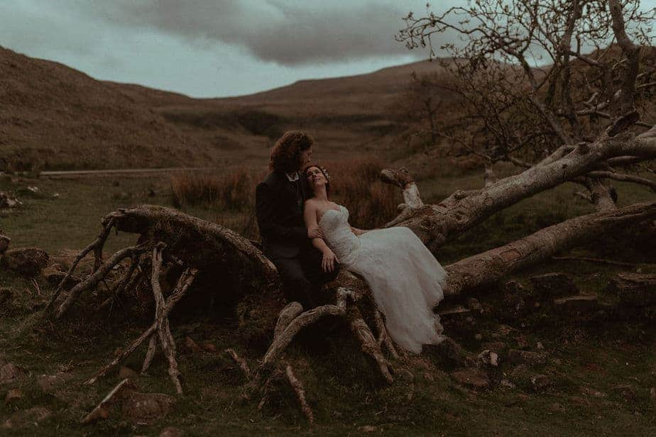 Couple Sat on Tree during Scotland Elopement by Scotland Elopement Photographer